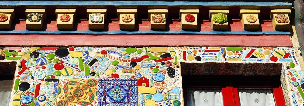 La vivace e coloratissima facciata della bottega del Maestro Testa, decorata con la ceramica, lungo la via principale del paese.