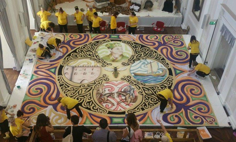 La realizzazione di una tradizionale infiorata durante il Palio di San Giovanni Battista