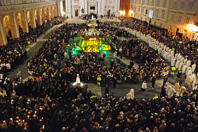 piazza colma di pellegrini con processione e, al centro, il presepe