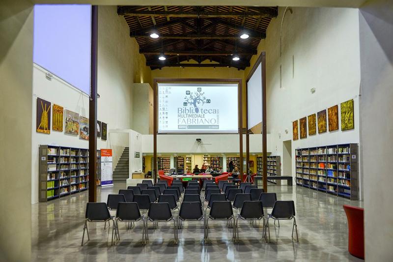 Interno di biblioteca, con sedie e maxi schermo