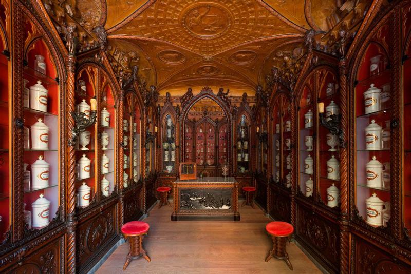 Interno di un edificio storico, tutto in legno, con scaffali e sedie