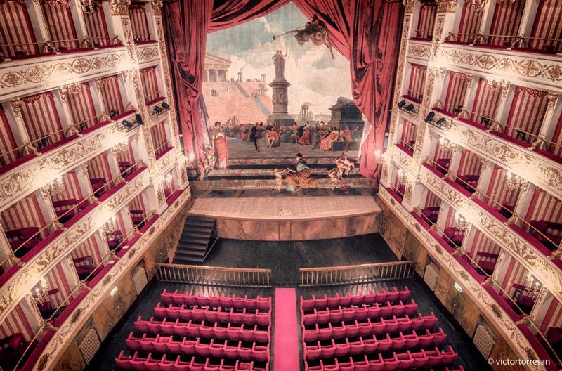 Interno del teatro, con palchi, sipario e sedie