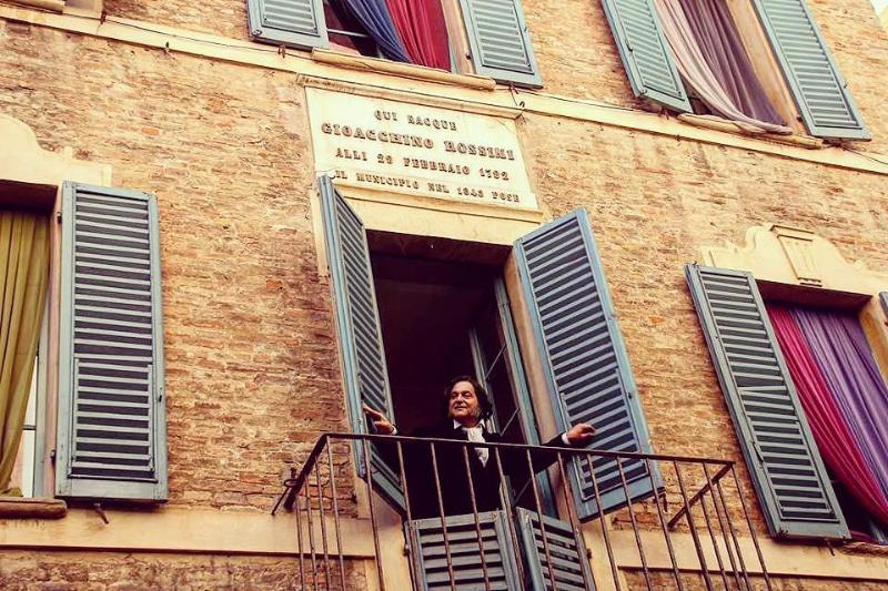 L'attore che interpreta Gioachino Rossini si affaccia dalla finestra della sua casa natale