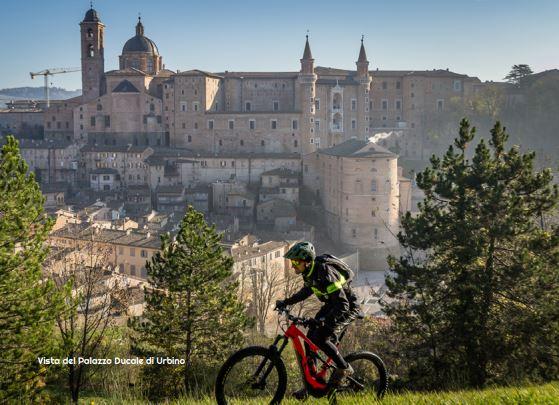 ciclista con sullo sfondo la città di Urbino