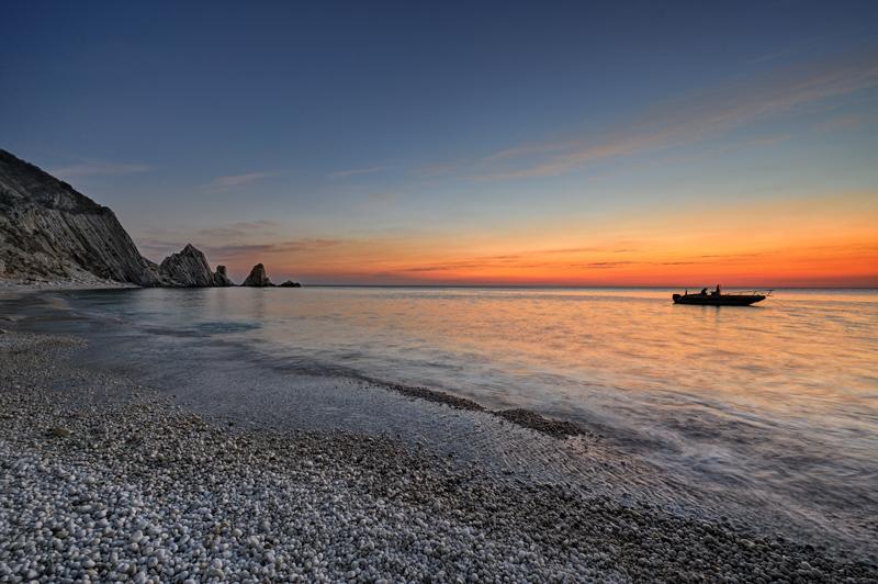 Panorama al tramonto, con canoa sulla destra e scogli sulla sinistra